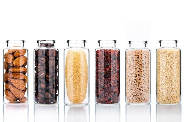 Natuurlijke alternatieve huidverzorging ingrediënten in glazen flessen isoleren op witte achtergrond.