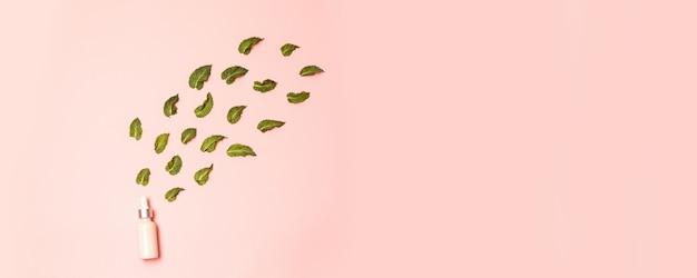 Natuurlijke anti-aging serum druppelaar in een glazen buis met muntblaadjes op roze