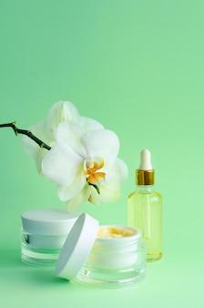 Natuurlijke anti-aging, voor jeugdcosmetica. crème, masker in pot, serum, vloeistof, olie in fles voor gezichtsverzorging, met orchideeën op groene muur. verticaal, patroon, kopieer ruimte