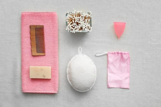 Natuurlijke badaccessoires met menstruatiecup op grijs. geen afvalconcept