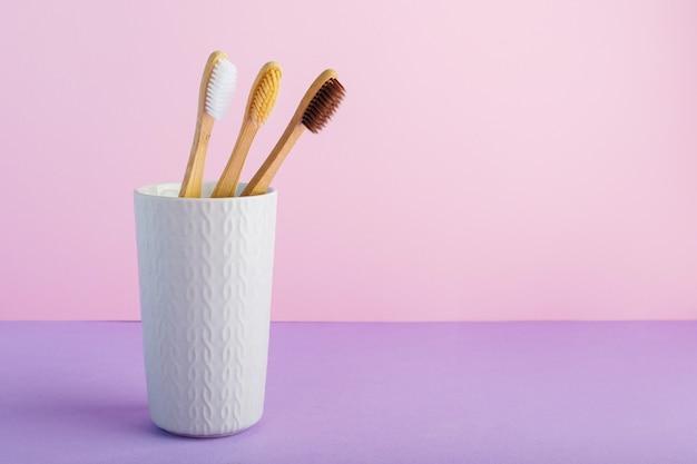 Natuurlijke bamboe tandenborstels in glas op kleur roze achtergrond. natuurlijke bamboe tandenborstel