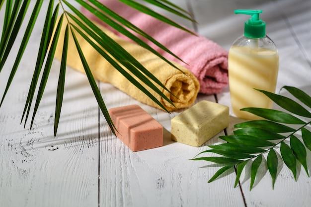 Natuurlijke biologische badproducten. handdoek, zeep, shampoofles en bladeren. schoonheid. mockup voor design