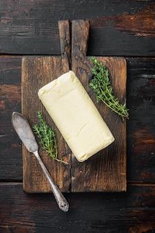 Natuurlijke biologische boter, voor het ontbijt, op oude donkere houten tafel achtergrond, bovenaanzicht plat lag