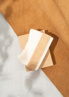 Natuurlijke biologische cosmetica. bovenaanzicht van handgemaakte zeep met ambachtelijke lege band op dubbele getextureerde lederen achtergrond met eucalyptus schaduw