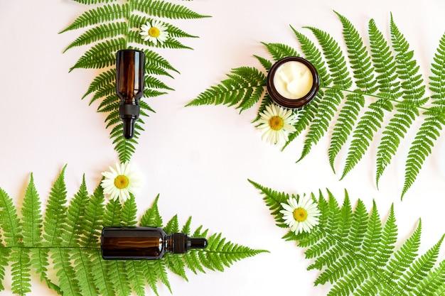 Natuurlijke biologische cosmetica met kruiden en kamille etherische olie met varenbladeren op witte achtergrond. huidverzorgingsroutine voor een gezonde huid