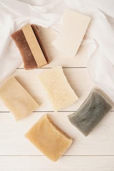 Natuurlijke biologische cosmetica. stapel handgemaakte zeep op witte houten ondergrond, mockup design
