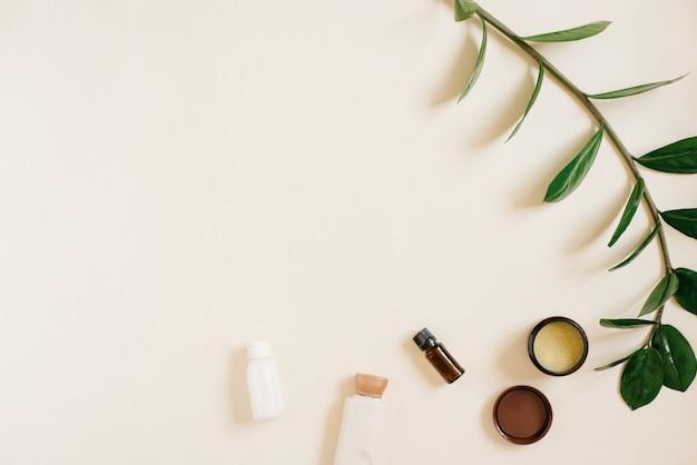 Natuurlijke biologische cosmetica voor lichaams- en gezichtsverzorging. flessen crème, een pot en een fles olie, een takje zamiokulkas. bovenaanzicht