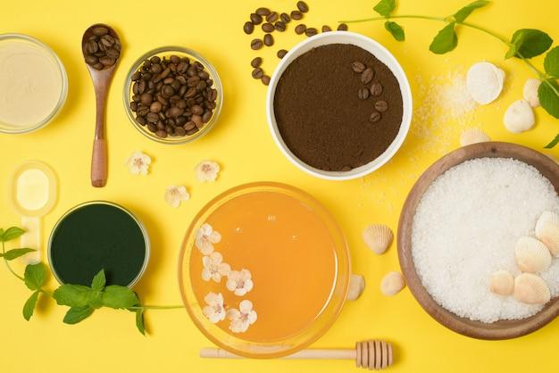 Natuurlijke biologische ingrediënten-zeezout, koffie scrub, honing en een harde body brush op een gele achtergrond. het uitzicht vanaf de top.
