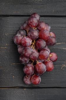 Natuurlijke biologische sappige druivenset, donkerrood fruit, op zwarte houten tafel, bovenaanzicht plat gelegd