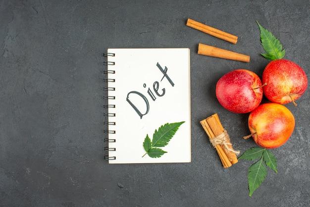 Natuurlijke biologische verse appels met groene bladeren, kaneellimoenen notitieboekje met dieetinscriptie op zwarte achtergrondbeelden