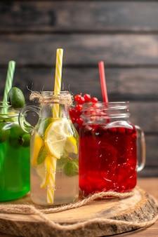 Natuurlijke biologische vruchtensappen in flessen geserveerd met buizen op een houten snijplank op een bruine tafel