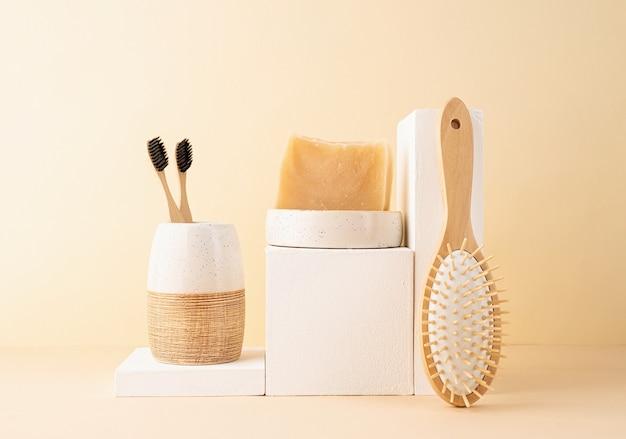 Natuurlijke biologische zelfzorgproducten. met de hand gemaakte zeep, houten borstel en bamboetandenborstels op witte podia. spa accessoires creatieve kunst compositie op beige achtergrond