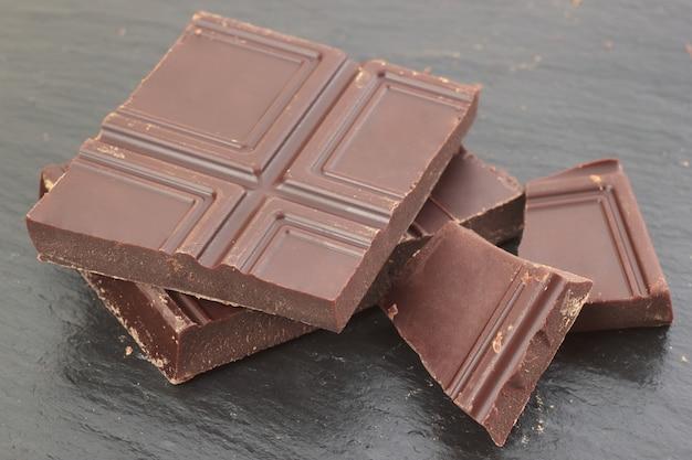 Natuurlijke bittere chocoladestukken op de achtergrond van de leiplaat