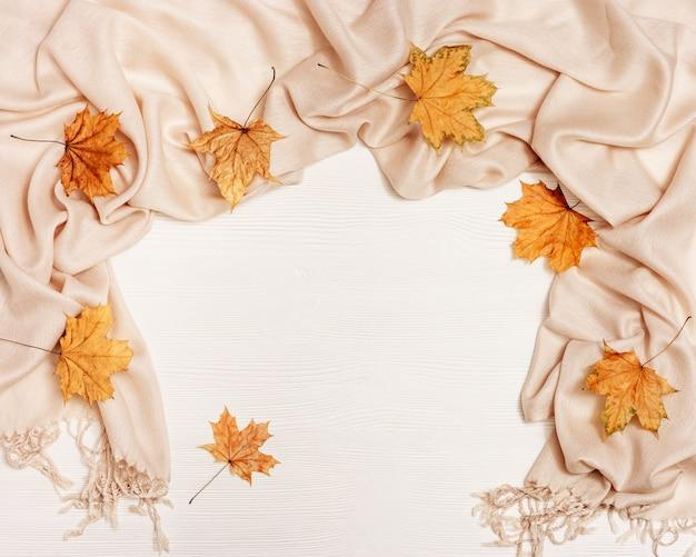 Natuurlijke bladeren van esdoorn en gezellige warme sjaal