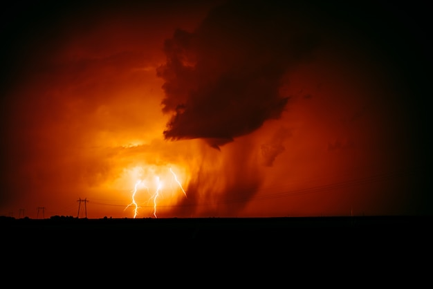 Natuurlijke bliksemschichtstaking in oranje hemel.