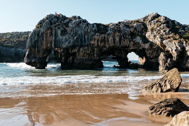 Natuurlijke boog van rotsen in het water bij de kust op een heldere dag