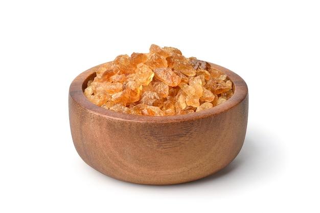 Natuurlijke bruine rotssuiker gemaakt van suikerriet in houten kom geïsoleerd op een witte achtergrond.