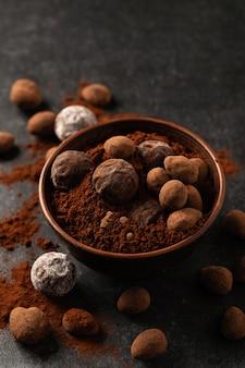 Natuurlijke chocoladetruffels in decoratieve gerechten, donkere achtergrond, sombere stemming