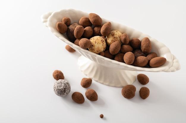 Natuurlijke chocoladetruffels in decoratieve gerechten, witte achtergrond