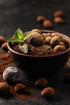 Natuurlijke chocoladetruffels met munt in decoratieve gerechten, close-up, donkere achtergrond, sombere stemming