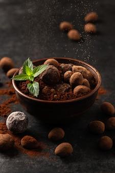 Natuurlijke chocoladetruffels met munt in decoratieve gerechten, donkere achtergrond, donkere sfeer
