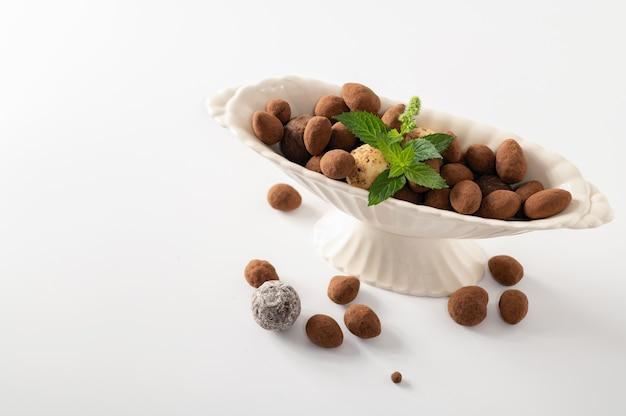 Natuurlijke chocoladetruffels met munt in decoratieve schotels, witte achtergrond