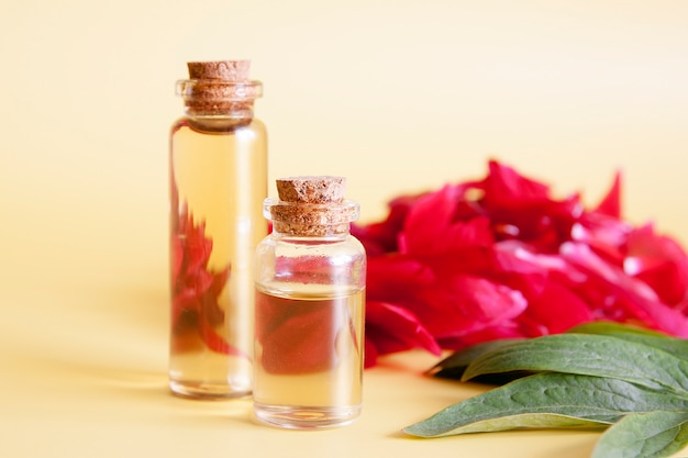 Natuurlijke cosmetica concept. glazen flessen met essentie van bloemblaadjes.