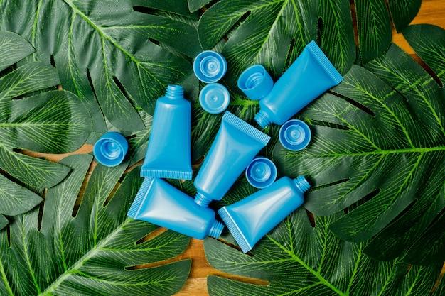 Natuurlijke cosmetica fles containers op groene blad achtergrond, lege fles, natuurlijke schoonheid huidverzorgingsproduct,