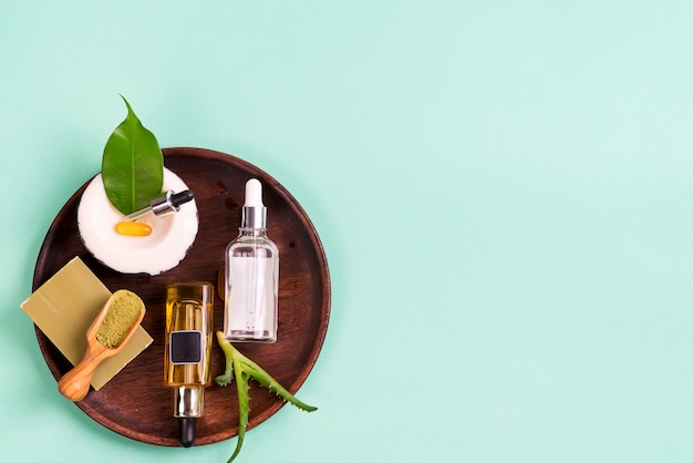 Natuurlijke cosmetica, oliën voor huidverzorging en natuurlijke zeep met bladeren en aloë vera in een houten plaat op een blauw