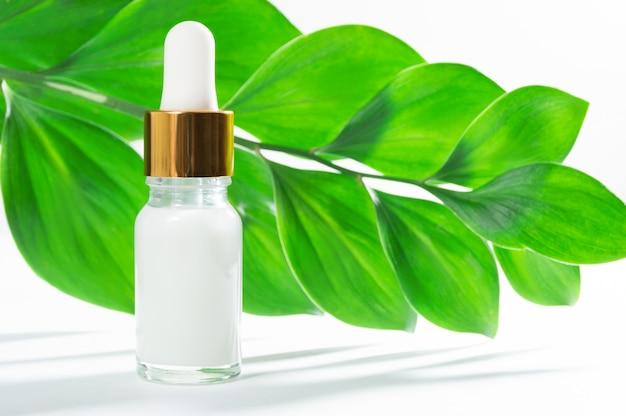 Natuurlijke cosmetica: serum met druppelaar en groene bladeren op witte achtergrond.