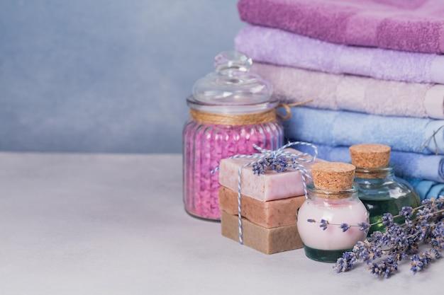 Natuurlijke cosmetische olie, room, zeezout en natuurlijke handgemaakte zeep met lavendel op lichte achtergrond. gezonde huidverzorging. aromatherapie, spa- en wellnessconcept