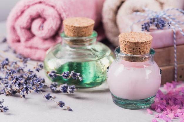 Natuurlijke cosmetische olie, room, zeezout en natuurlijke handgemaakte zeep met lavendel op lichte achtergrond. gezonde huidverzorging. aromatherapie, spa- en wellnessconcept Premium Foto