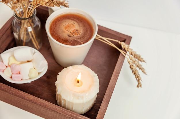 Natuurlijke eco home decor met kopje koffie marshmallow en kaars op houten dienblad