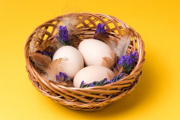 Natuurlijke ecologische eieren, veren en lavendel in een rieten mand op gele achtergrond met kopie ruimte. gelukkig pasen