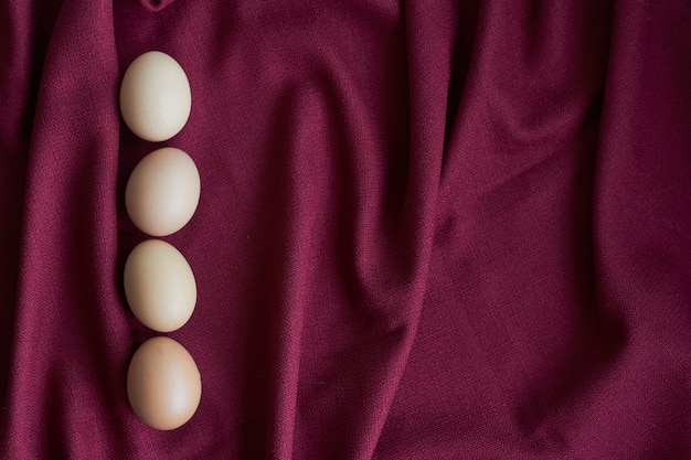 Natuurlijke eieren op rood tafelkleed, verschillende bruine kippeneieren liggen op bordeauxrood tafelkleed