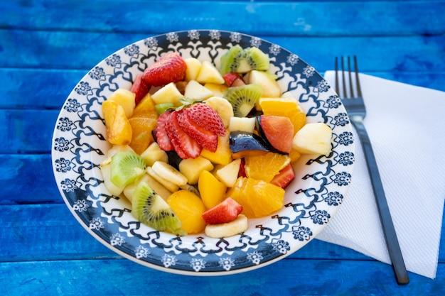 Natuurlijke en gezonde fruitsalade met sinaasappel in een vintage plaat op een rustiek blauw oppervlak.