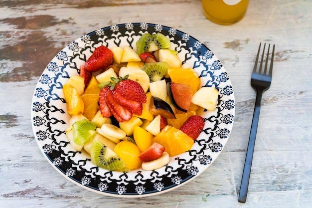 Natuurlijke en gezonde fruitsalade met sinaasappel in een vintage plaat, op een rustieke ondergrond.