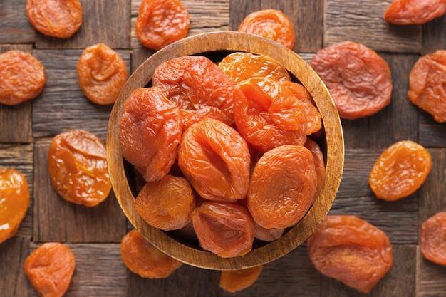 Natuurlijke gedroogde abrikozen in houten kom, bovenaanzicht.