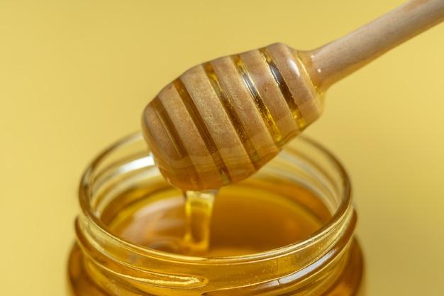Natuurlijke gezonde bijenhoning in een potje en op een houten stokje