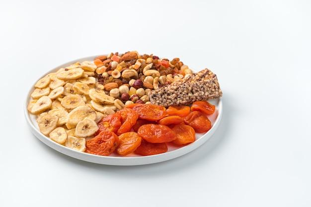 Natuurlijke, gezonde snoepjes met een plat bord op een witte muur. zijaanzicht, kopieer ruimte.
