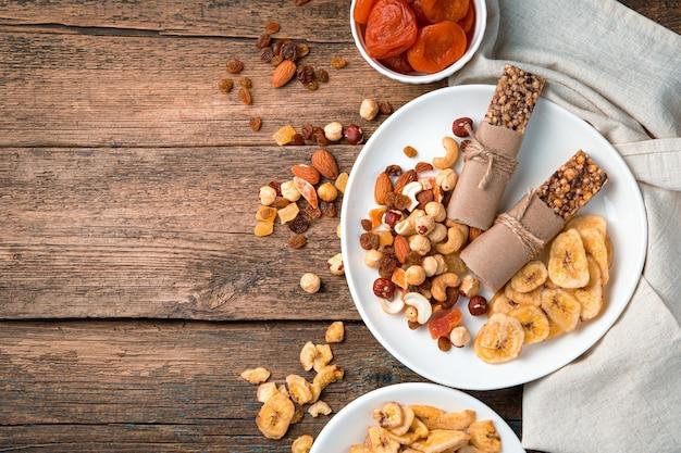 Natuurlijke, gezonde snoepjes. mueslireep, noten, gedroogde vruchten in een witte plaat op een houten bruine muur. bovenaanzicht.