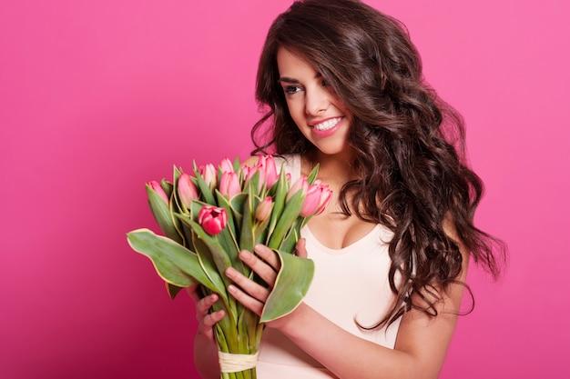 Natuurlijke glimlachende vrouw met boeket verse tulpen