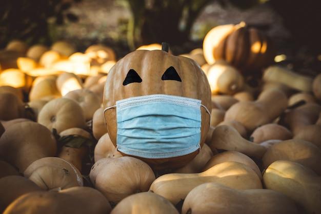Natuurlijke halloween-pompoen gemaskeerd door de pandemie van het coronavirus