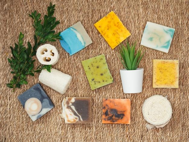 Natuurlijke handgemaakte huidverzorging. biologische stukken zeep met plantenextracten. stapelt zelfgemaakte stukken zeep met kruidenmateriaal. natuurlijke zeep met spa-accessoires.