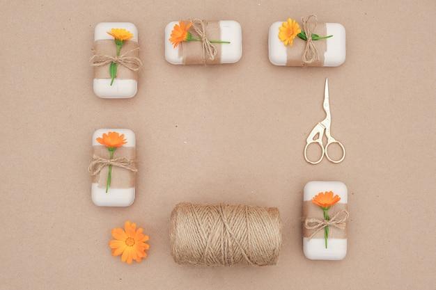 Natuurlijke handgemaakte zeep, versierd kraftpapier, blauwe bloem, streng van touw en schaar, kaderrand organische cosmetica,