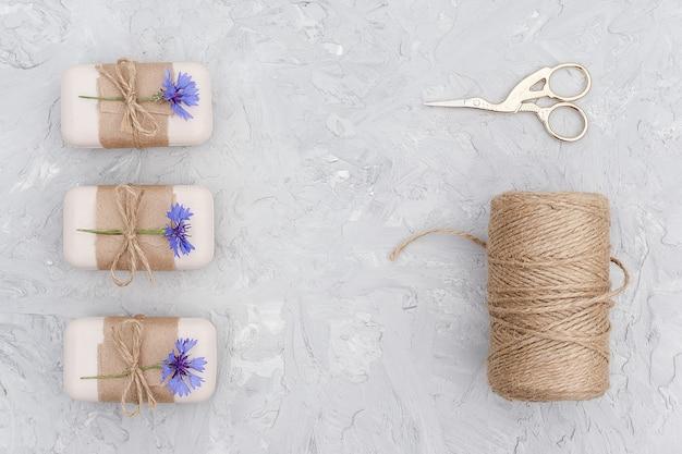 Natuurlijke handgemaakte zeep, versierd kraftpapier, blauwe bloem, streng van touw en schaar.