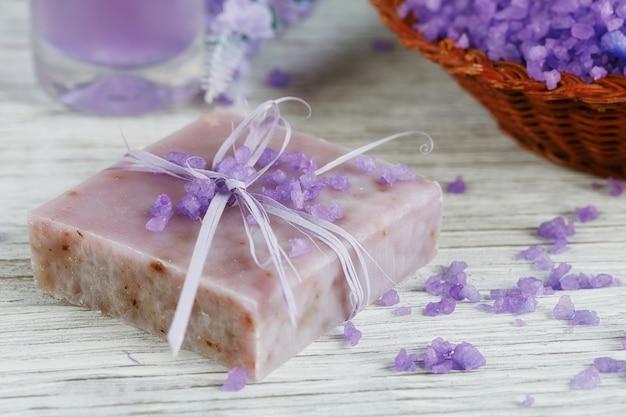 Natuurlijke handgemaakte zeep, zeezout en handdoek op een witte houten ondergrond