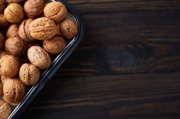 Natuurlijke hele walnoten op donkere houten tafel. bovenaanzicht, plat gelegd met kopieerruimte