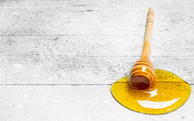 Natuurlijke honing met een houten lepel. op een rustieke tafel.