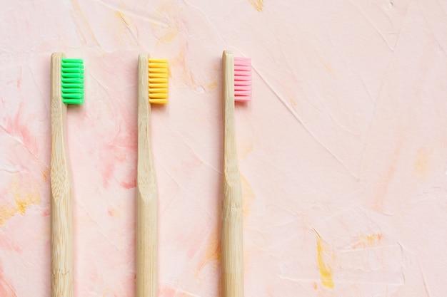 Natuurlijke houten bamboe tandenborstels op roze oppervlak